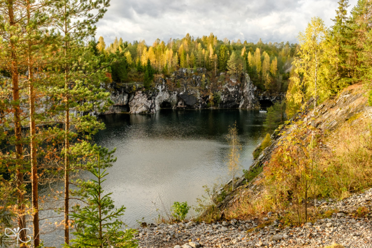 Forest at Large marble quarry lake is highlighted with sunset